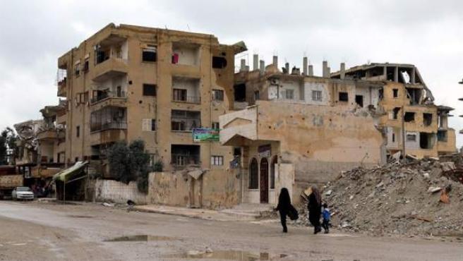 Dos mujeres caminan con un niño junto a casas derruidas en Al Raqa, ciudad que fue la capital de facto de Estado Islámico en Siria hasta la expulsión de los yihadistas.