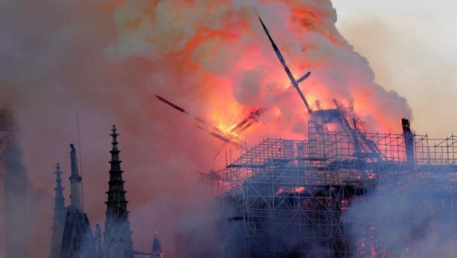 La aguja central de la catedral de Notre Dame cae durante el incendio este lunes en París, Francia.