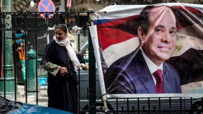Una mujer camina junto a un cartel con la imagen del actual presidente egipcio y candidato presidencial, Abdelfatah al Sisi, en El Cairo.