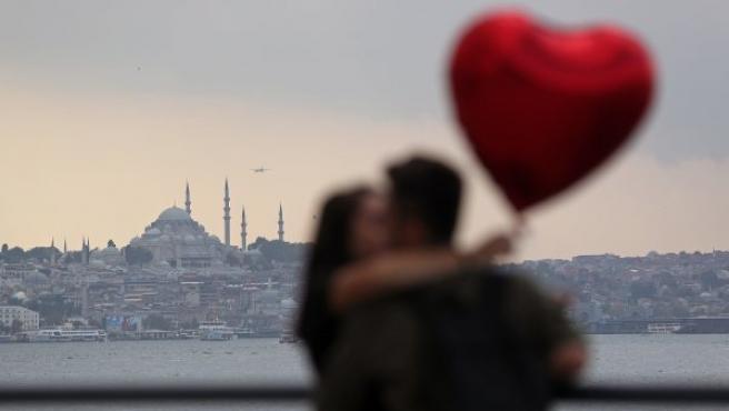 Una pareja se besa frente al Estrecho del Bósforo con la mezquita de Süleymaniye como escenario de fondo, en Estambul (Turquía).
