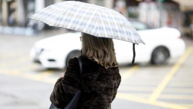 Imagen de una mujer con paraguas debido a la lluvia.