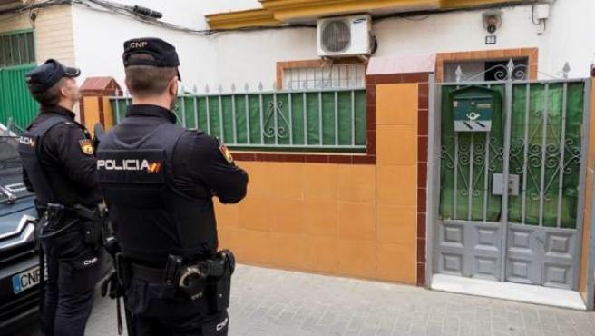 Dos agentes de la Policía Nacional, durante el registro de la casa de Sevilla donde residía el presunto yihadista que supuestamente tenía previsto atentar en la capital andaluza y que fue detenido en Marruecos.