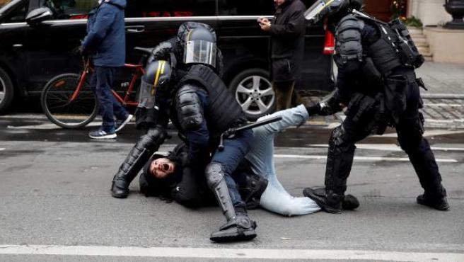 Agentes antidisturbios cargan y arrestan a un hombre durante la manifestación de los 'chalecos amarillos' en París.