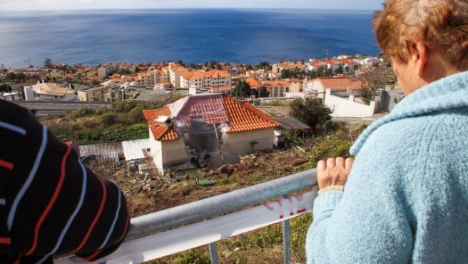Un hombre y una mujer observan el lugar donde se accidentó un autobús en Canico, Santa Cruz, Madeira.