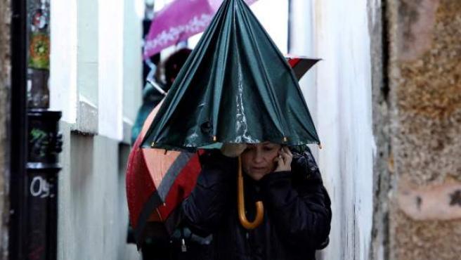 Turistas se protegen de la lluvia en Santiago de Compostela.