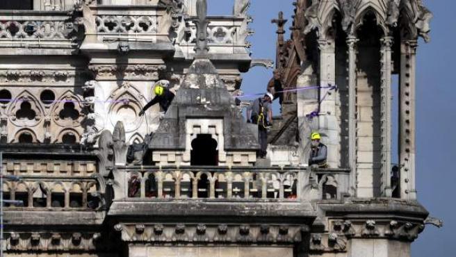 Operarios inspeccionando las partes altas de la catedral de Notre Dame, en París.