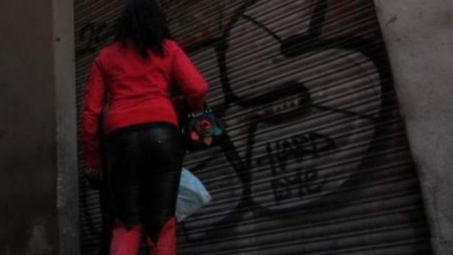 Una prostituta junto a una vivienda.