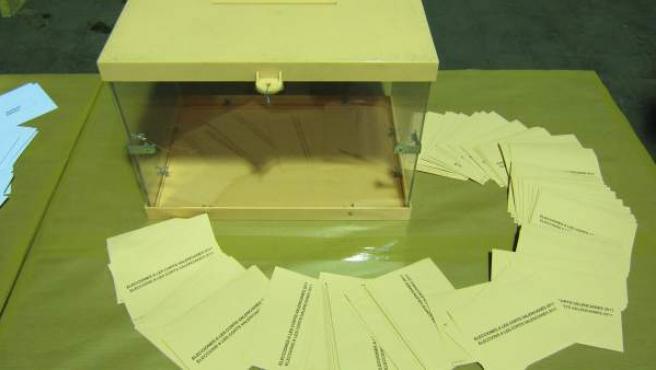 Un puñado de papeletas junto a una urna.
