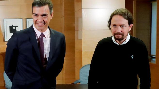 Pedro Sánchez, con el líder de Podemos, Pablo Iglesias, vestido con jersey negro.