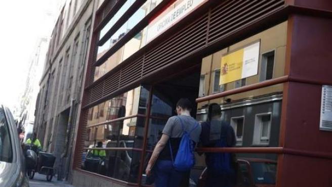 Un joven se apoya en la entrada de una oficina de empleo.