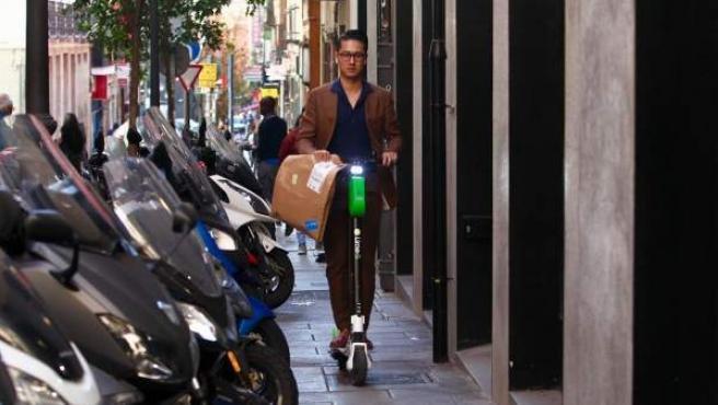 Una persona conduce un patinete eléctrico en Madrid.