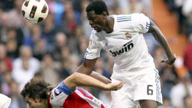 Emmanuele Adebayor, delantero del Real Madrid, remata de cabeza ante Iván Hernández, defensa del Sporting.