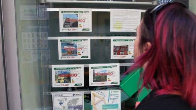 Una mujer observa ofertas de pisos para alquilar o comprar.