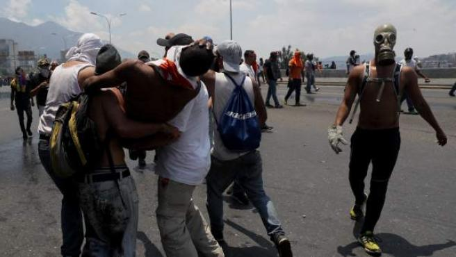 Un grupo de personas cargan un herido durante una manifestación en apoyo al presidente de la Asamblea Nacional, Juan Guaidó.