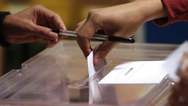 Detalle de una papeleta entrando en una urna.