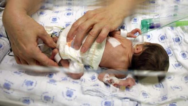 Un bebé prematuro recibe cuidados en una incubadora.