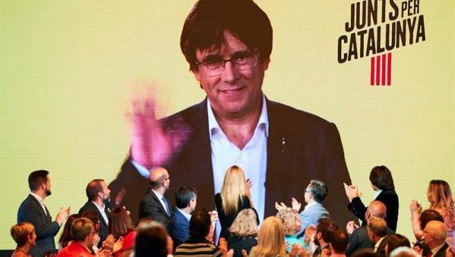 El expresidente de la Generalitat Carles Puigdemont interviene por videoconferencia en el acto de inicio de campaña de JxCat, en Barcelona.