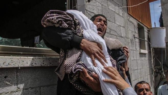Un pariente de la niña palestina Seba Abu-Arrar, de 14 meses de edad, lleva su cuerpo durante su funeral en el vecindario de Al-Zaitun, al este de la ciudad de Gaza.