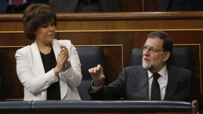 Mariano Rajoy es aplaudido por Soraya Sáenz de Santamaría durante la segunda jornada de la moción de censura.