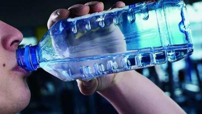 Un hombre bebe agua de una botella de plástico.