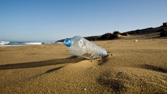 Botella de plástico en la arena de la playa.