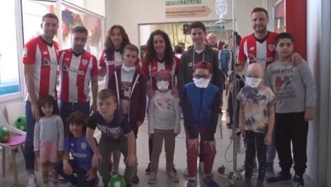 Los jugadores y jugadoras del Athletic Club junto a los niños del Hospital de Cruces