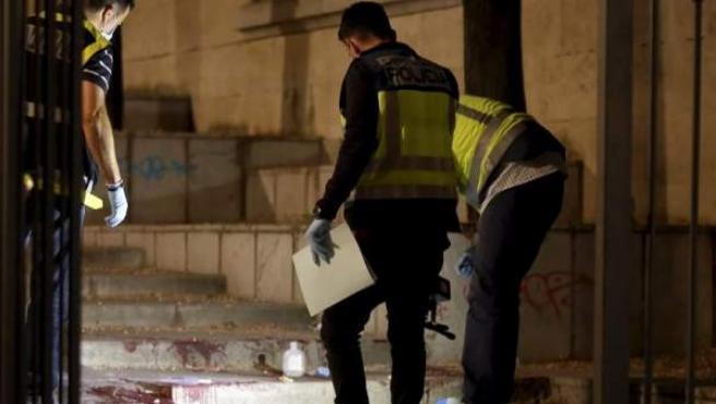 Agentes de la policía científica inspeccionan el lugar donde un hombre hirió de gravedad con arma blanca a su supuesta expareja, en la Plaza de la Libertad de Granada.