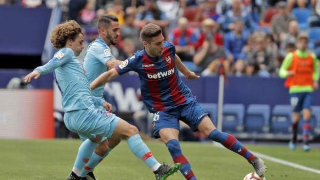 El centrocampista del Levante Rubén Rochina defiende el balón ante los jugadores del Atlético de Madrid Antoine Griezmann y Koke Resurrección.