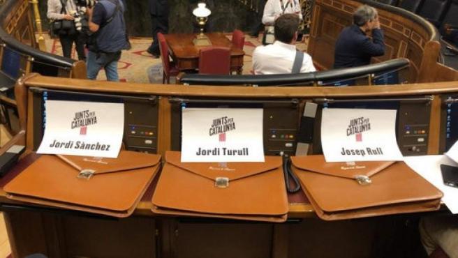 Las carteras de Sànchez, Rull y Turull con sus carteles, en los escaños 'reservados' por JxCat en el Congreso, en el inicio de la XIII Legislatura.