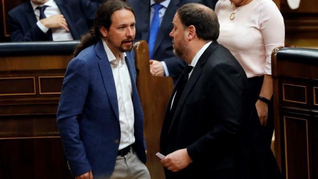 El líder de Podemos, Pablo Iglesias (i), conversa con el diputado electo en prisión preventiva de ERC, Oriol Junqueras (d), durante la sesión constitutiva de las nuevas Cortes Generales.