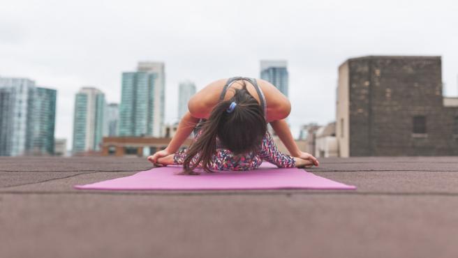 Una mujer practica ejercicios de yoga en una azotea.