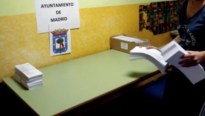 Trabajadores preparan las mesas electorales en un colegio público madrileño.