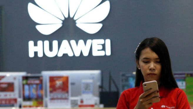 Una empleada de Huawei revisa un teléfono en una tienda de la marca en Bangkok.