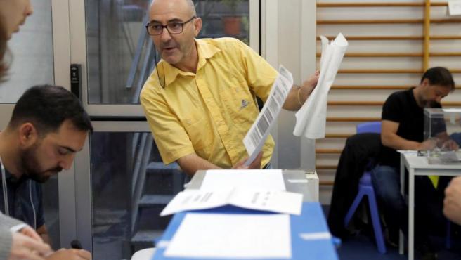 Un funcionario de Correos entrega las votaciones en colegio electoral de Madrid.