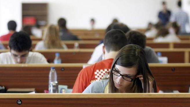 Varios jóvenes universitarios, estudiando en una biblioteca.