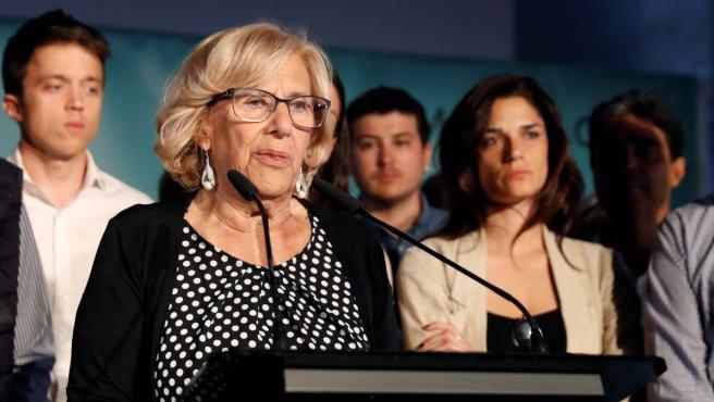 La alcaldesa de Madrid, Manuela Carmena, durante su comparecencia esta noche para valorar los resultados de las elecciones al Ayuntamiento. Al fondo, el candidato a la Comunidad de Madrid Íñigo Errejón (izda).
