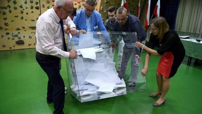 Varias personas vacían una urna electoral tras la celebración de los comicios europeos, en Przemysl, Polonia.