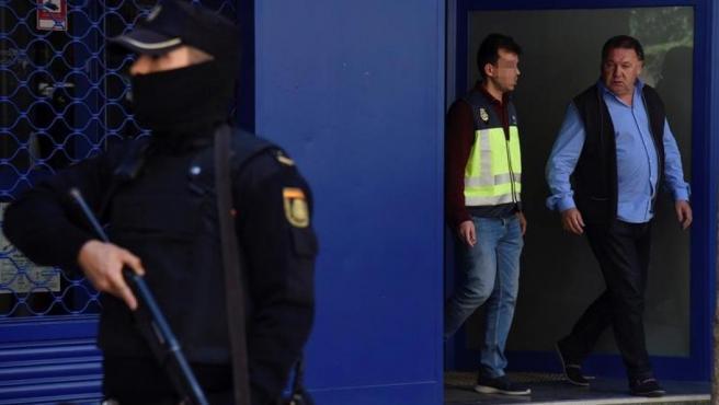 El presidente del Huesca, Agustín Lasaosa, junto a un policía, a su salida de las oficinas del club tras ser detenido durante la 'Operación Oikos'.