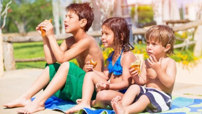 Tres niños disfrutando de su merienda en la playa.