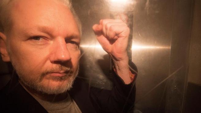 El fundador de WikiLeaks, Julian Assange, saluda a los fotógrafos mientras abandona en un vehículo policial el tribunal de Southwark, en Londres (Reino Unido).