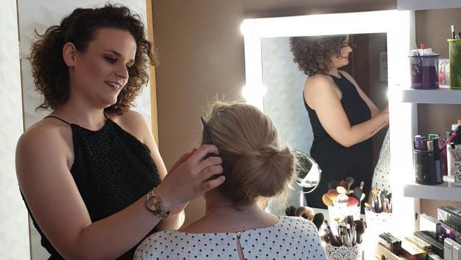 Alejandra Gallego, enferma de esclerosis múltiple, maquilla a una clienta.