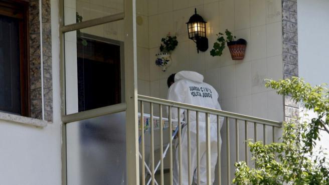 Un miembro de la Guardia Civil trabaja en el domicilio de la localidad asturiana de Degaña.