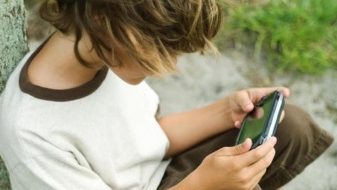 Un niño jugando con su consola portátil.