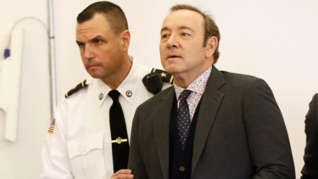 El actor Kevin Spacey (d) es acompañado por un oficial de la corte cuando comparece ante el Tribunal de Distrito de Nantucket, en Nantucket, Massachusetts, EE UU.