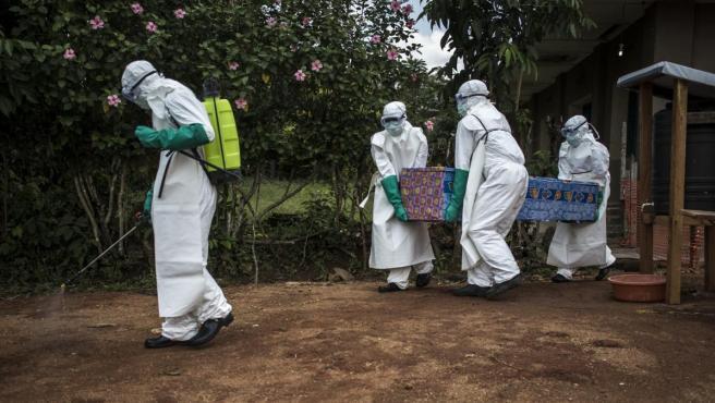 Personal sanitario carga con el ataúd de una víctima de ébola en la República Democrática del Congo.