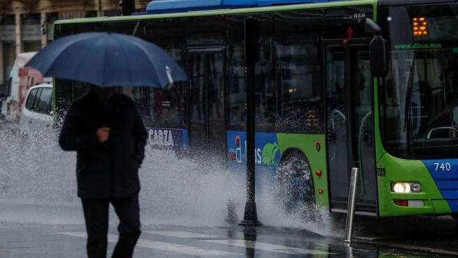 Un hombre se protege de la lluvia en San Sebastián.