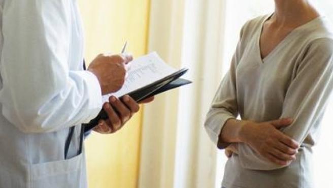 Un médico pasa consulta a una paciente.
