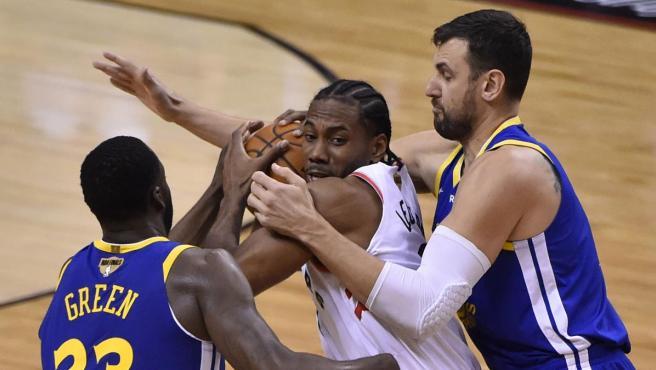 Kawhi Leonard, estrella de Toronto Raptors, rodeado por dos jugadores de Golden State Warriors.