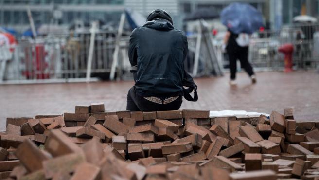 Un manifestante sentado sobre una pila de adoquines en las protestas de Hong Kong.