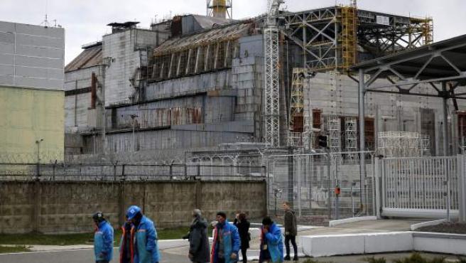 Un grupo de trabajadores ucranianos pasa por delante de la central nuclear de Chernóbil.